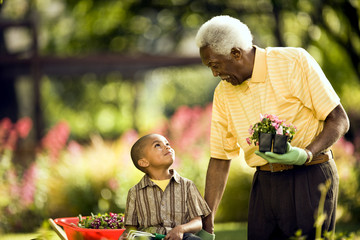 Senior man gardens with his young grandson.