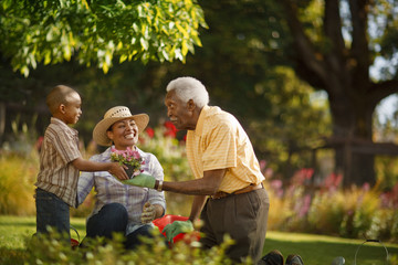 Grandfather bonding with his daughter and grandson in the garden.