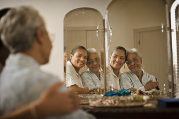 Elderly woman and daughter looking into mirror.
