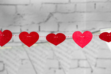 Small Red Hearts with Stitches Hanging on a String with Clothespin above wall on Light gray Background