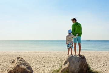 Father and young son have fun at beach.