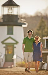 Husband and wife walking in front of lighthouse.