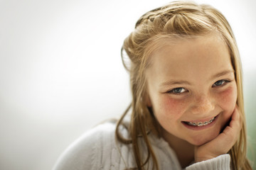 Portrait of a smiling young girl with her hand on her chin.