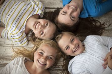 Portrait of four smiling sisters lying on the floor with their heads together.