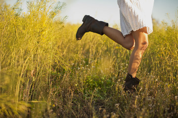 Woman in a white dress and cowboy boots dancing in a meadow.