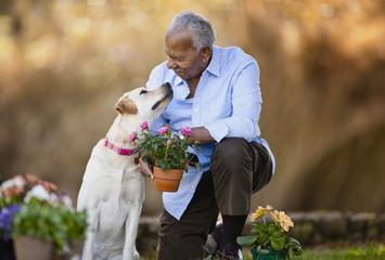 Senior man looking at his dog while arranging pot plants.