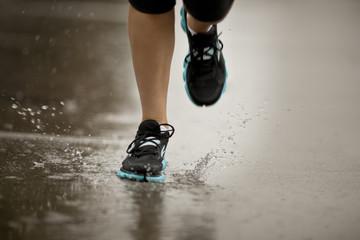 Young woman jogging on a residential street in the rain.