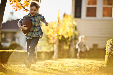 Running boy playing football in the backyard with his brother.