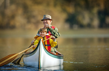 Grandfather canoeing on river with grandson.