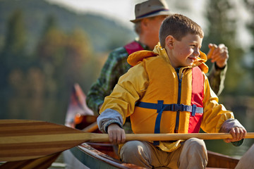 Happy grandfather and young grandson canoeing together on a lake.
