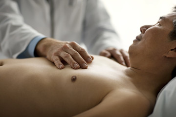 Doctor lays a comforting hand on a patient's bare chest.