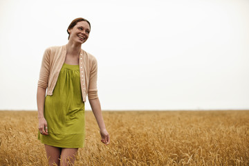 Teenage girl enjoys strolling through the wheat field.