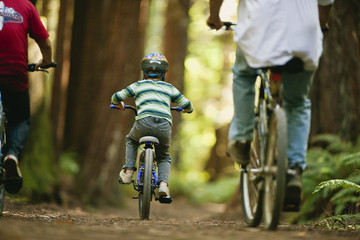 Boy riding his bicycle through the forest with his brother and father.
