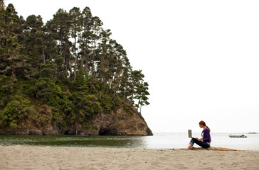 Teenage girl sitting at the beach and using her laptop.