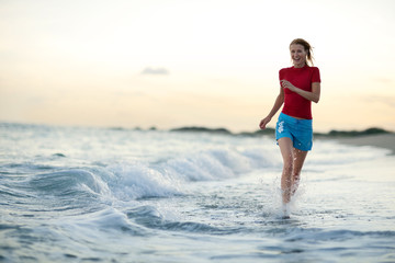 Mid-adult woman running in water at the beach.