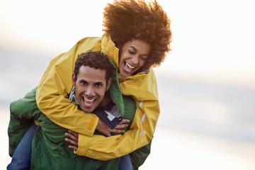 Mid adult man giving his girlfriend piggyback ride.