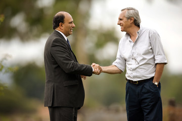 Businessman and farmer shaking hands.