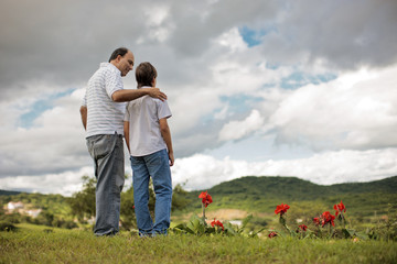 Mature man walking through field with his young son.