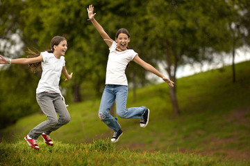Two girls excitedly jumping in air.