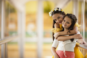Smiling girl standing with arms around sister.