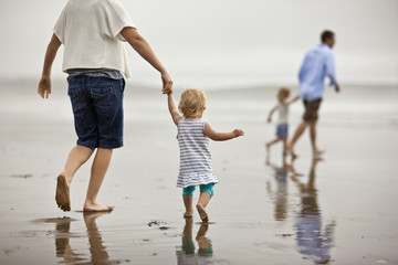 Couple walking hand in hand with their daughters on a beach at low tide.
