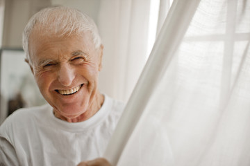 Portrait of a laughing senior man next to a curtained window.