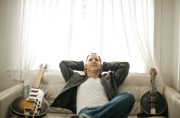 Mid-adult man sitting on a couch with two guitars in his living room.
