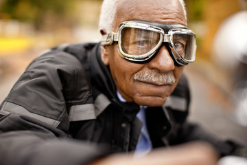 Portrait of a senior man sitting on a motorcycle wearing riding goggles.