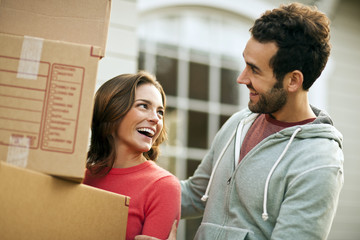 Mid-adult couple carry moving boxes.
