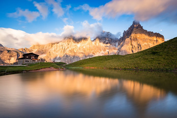 Photo sur Plexiglas Reflexion The Pale di San Martino peaks (Italian Dolomites) reflected in the water at sunset, with an alpine chalet on background.