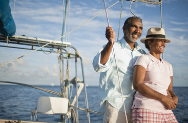 Mature couple enjoying view of water from boat deck.