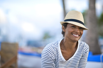 Portrait of mature woman smiling wearing fedora.