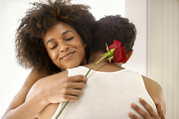 Young woman hugging her boyfriend while holding the rose.