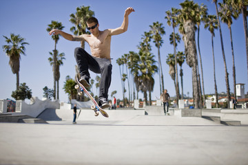 Teenage boy doing jump on a skateboard