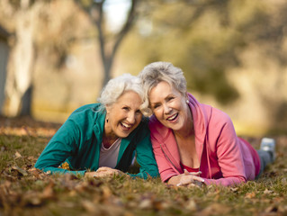 Two active senior women lying side by side in a park.