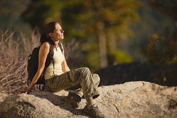 Backpacker sitting on rock and enjoying the view from mountain top.