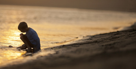Young boy sitting with his leg in the water at a beach.