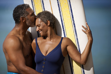 Man kissing his wife's head, as she holds surfboard.