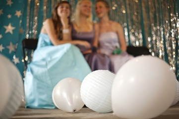 Three teenage girls sitting on chairs, balloons and lanterns covering the floor of a prom.
