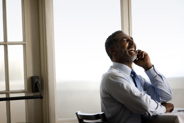 Businessman laughing as he talks on cell phone.