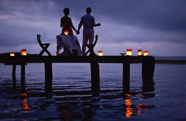 Mature couple enjoying their date on the pier at twilight.
