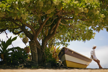 Mature woman sitting on dinghy under the tree at the beach.