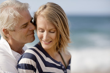 Mid adult woman being affectionate with her husband on the beach.