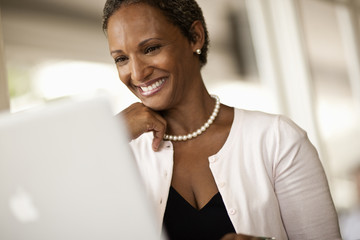 Smiling businesswoman working at her laptop.