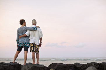 Couple standing together on rocks with arms around each other.
