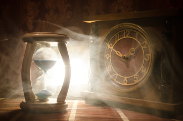 Time concept. Silhouette of Hourglass clock and old vintage wood clock with arrow and smoke on dark background with hot yellow orange red blue cold back lighting, or symbols of time with copy space