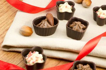 chocolate candy with nuts on burlap with a red ribbon