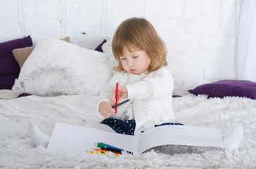 Smiling little girl drawing in bed сolored pencils