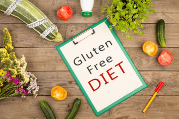 """Diet plan - marrow squash, clipboard with text """"Gluten Free DIET"""", vegetables and measuring tape"""