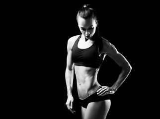 Young sporty woman posing on black background. Black and white photo